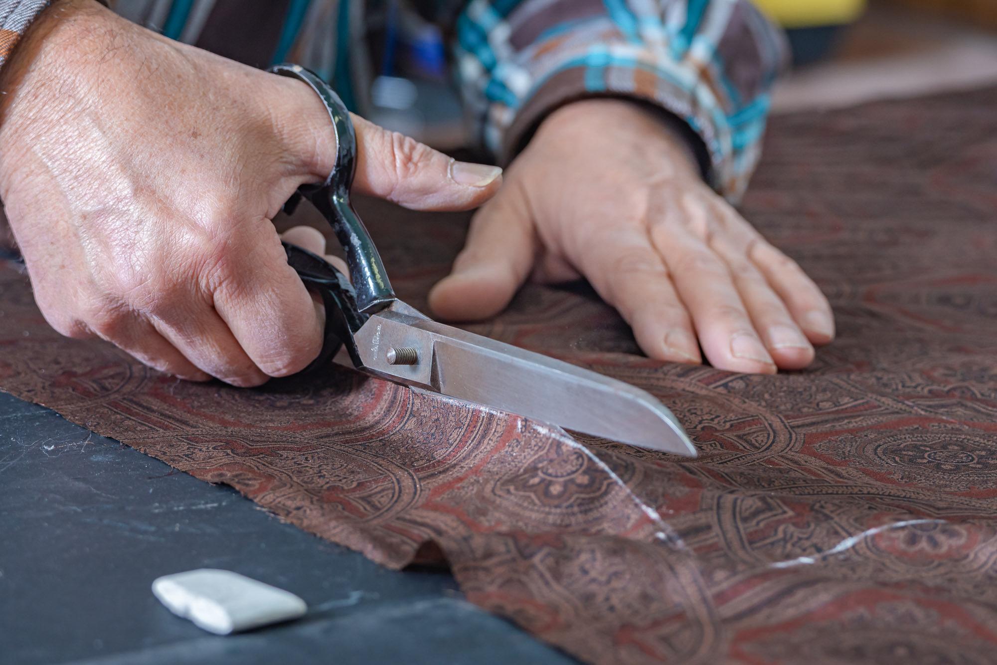 Interpel - Dettaglio di mani che tagliano la pelle